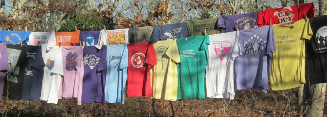 A couple dozen T-shirts hanging on two clotheslines
